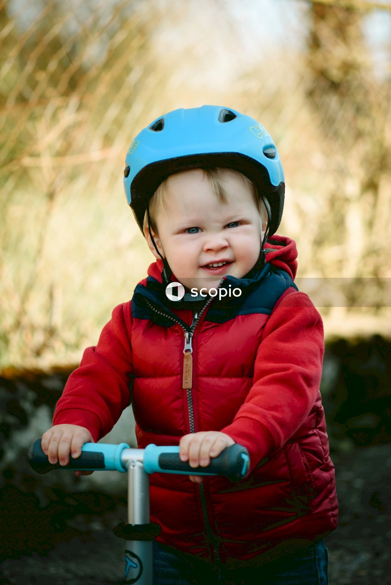 Child in blue jacket riding bicycle