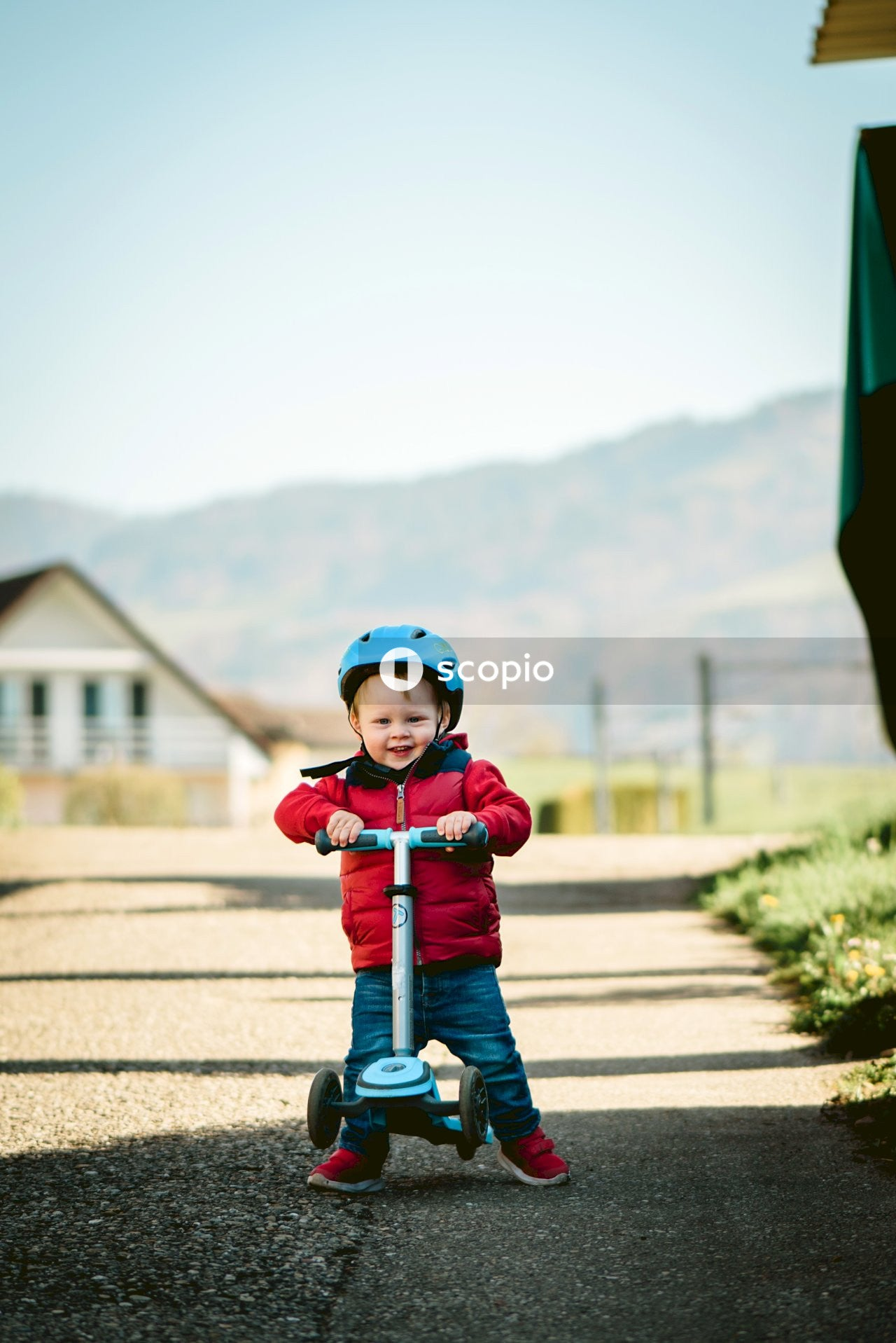 Child in red jacket and blue denim jeans riding on kick scooter