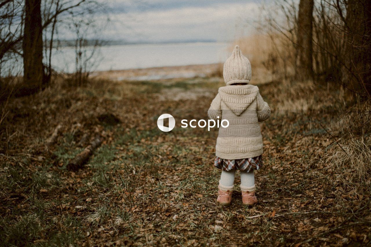 Child in white knit cap and white and brown plaid coat standing on brown dried leaves