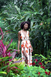 Woman in white and orange floral dress standing near green plants