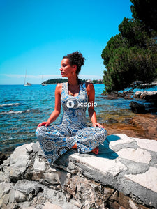 Woman in blue and white floral spaghetti strap dress sitting on rock near body of water