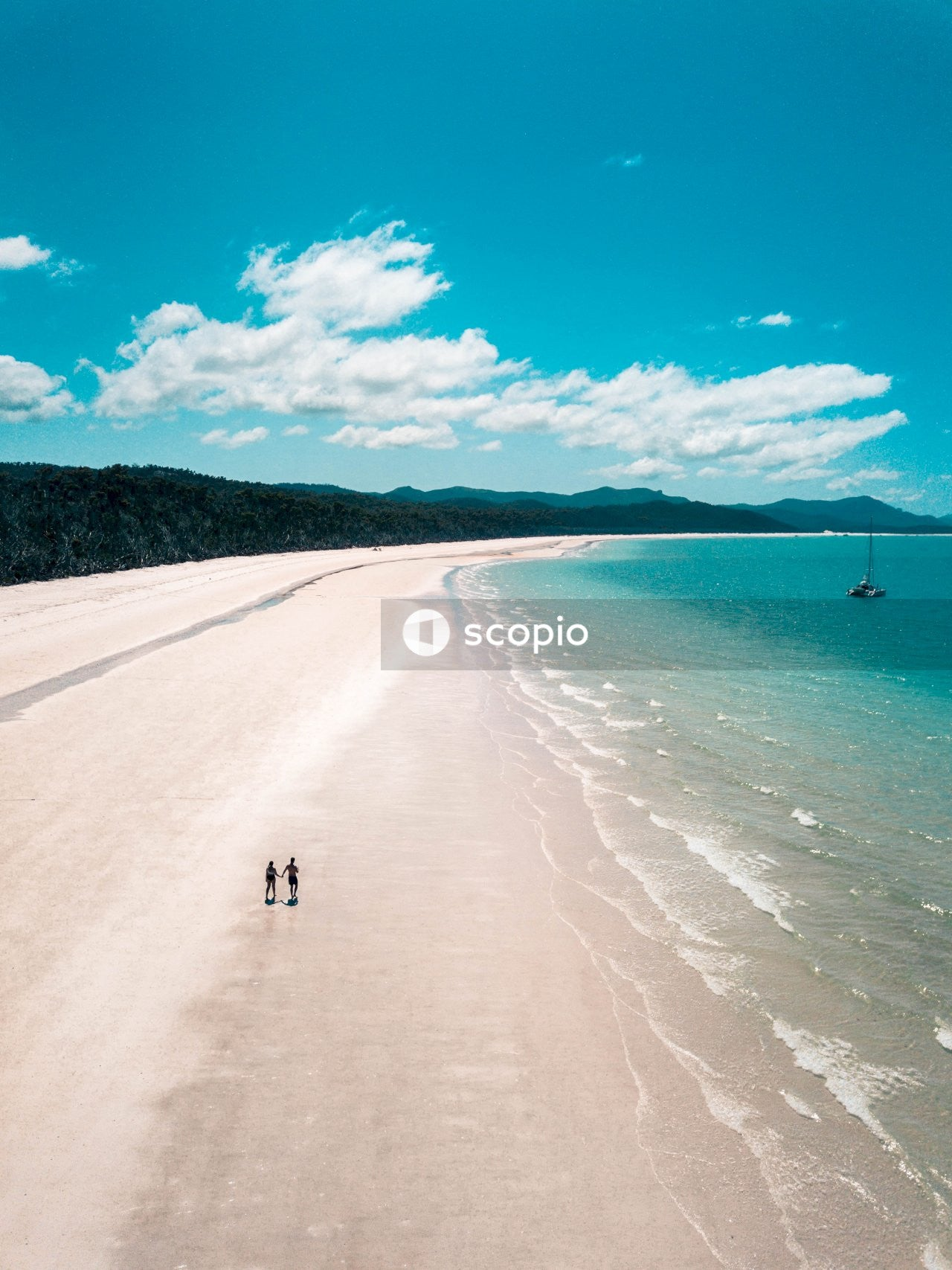 People walking on white sand beach