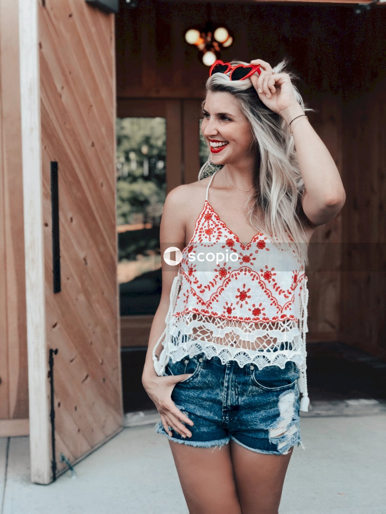 Woman in red and white floral tank top and blue denim shorts