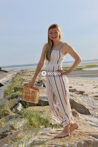 Woman in white and red stripe spaghetti strap dress holding brown woven basket on beach