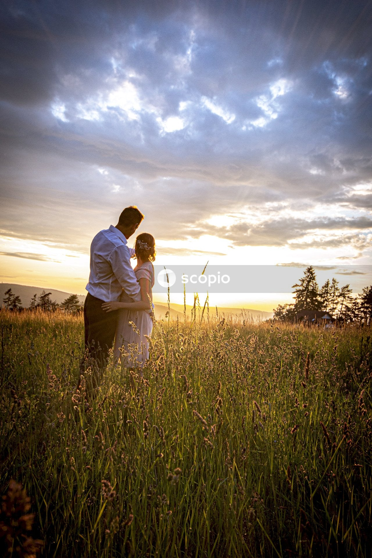 Man hugging woman under cloudy sky