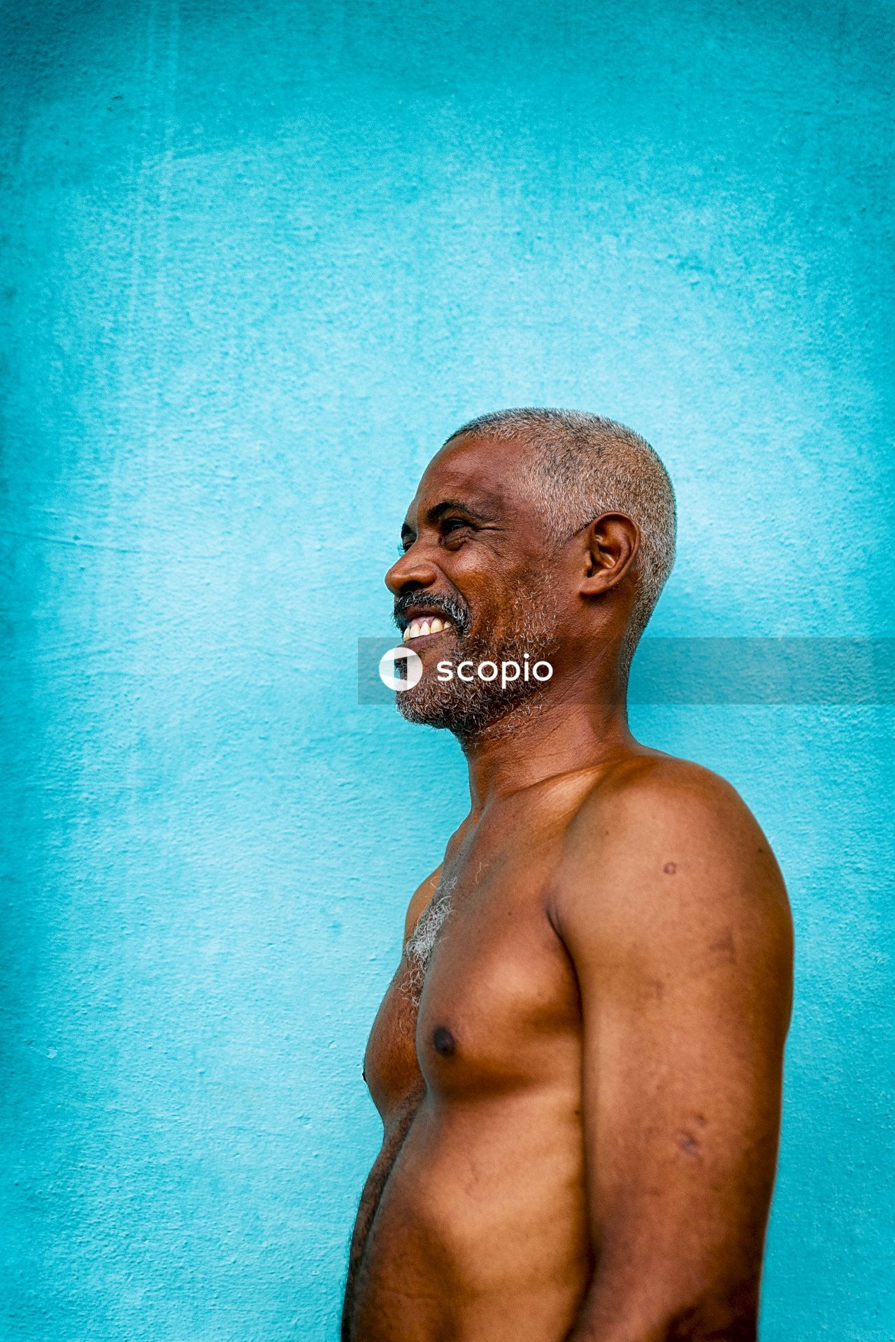 Topless man standing against blue wall