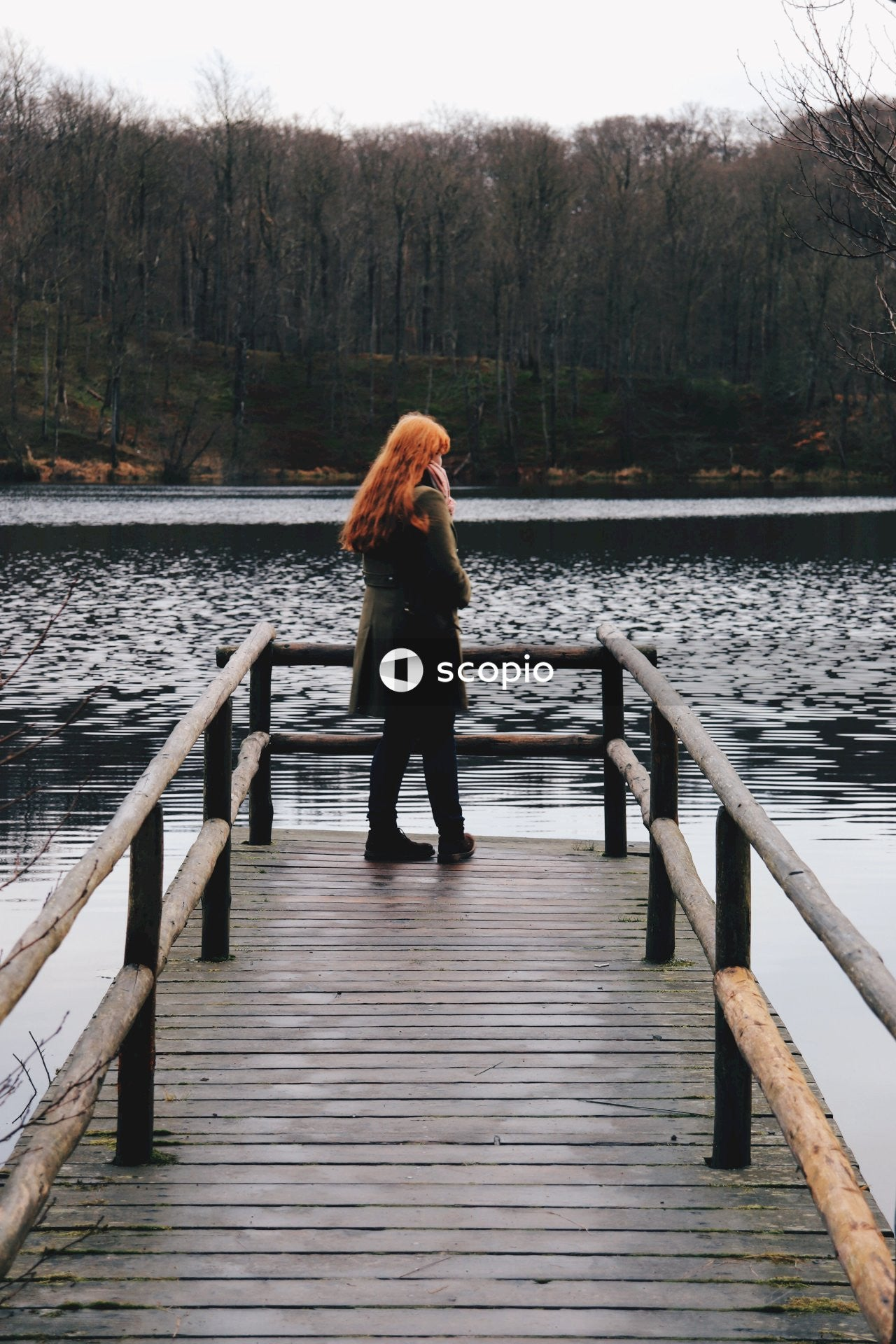 Woman in black long sleeve shirt and black pants standing on wooden dock
