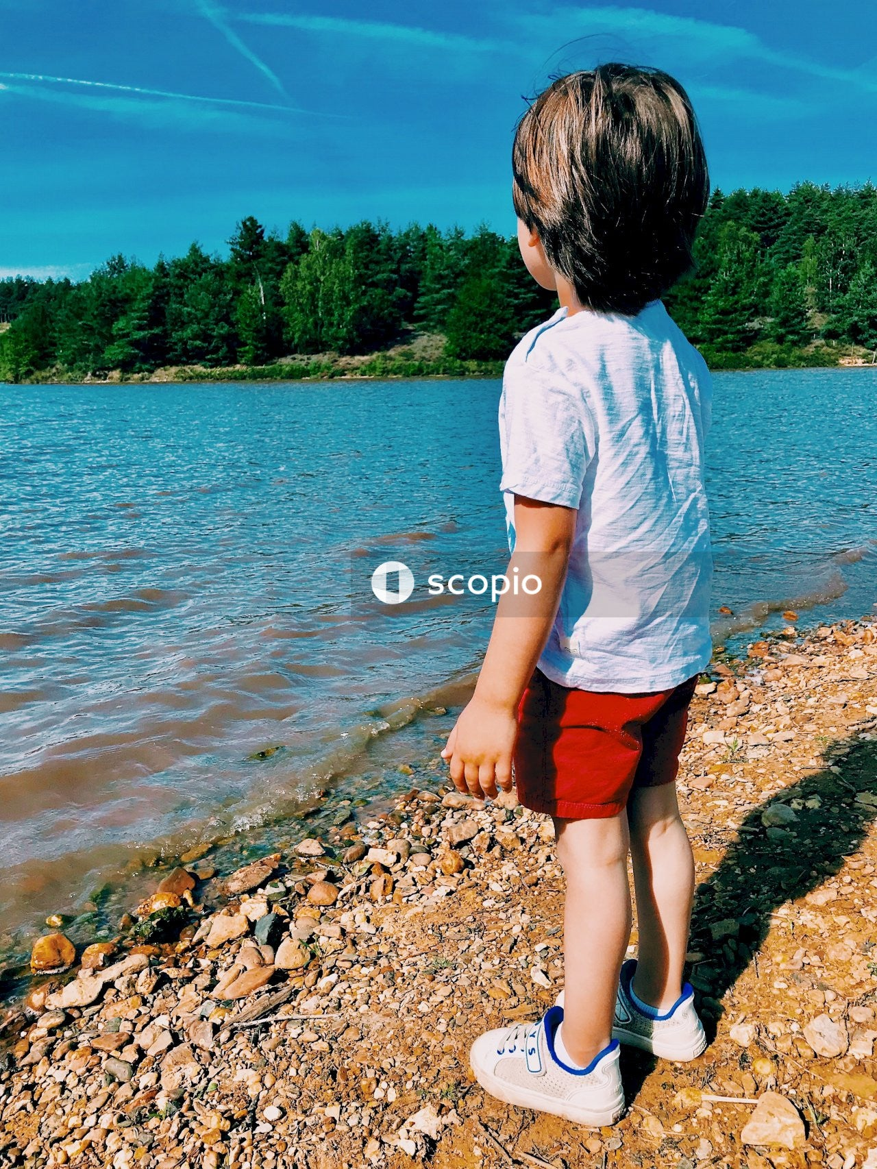 Child wearing white t-shirt standing and facing on body of water