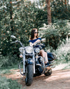 Woman riding cruiser motorcycle parked on dirt road