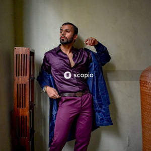 Man in blue button up long sleeve shirt and purple pants standing beside brown wooden door