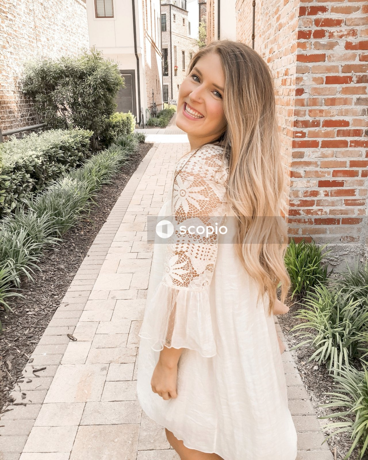 Woman in white and brown floral long sleeve dress standing on brick pathway