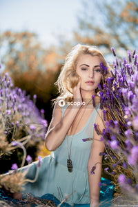 Woman in white tank top holding purple flower