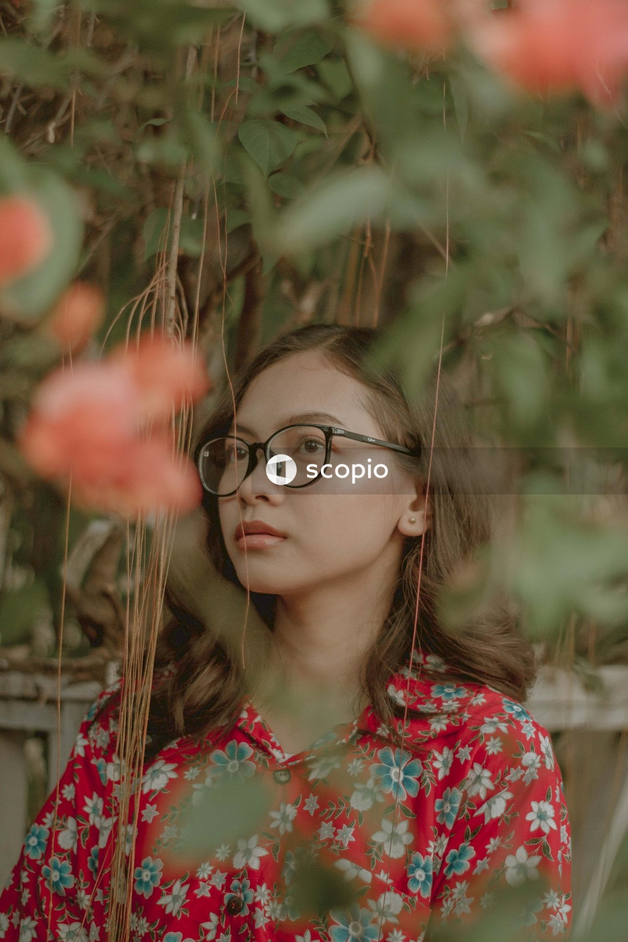 Woman in red and white floral shirt wearing black framed eyeglasses
