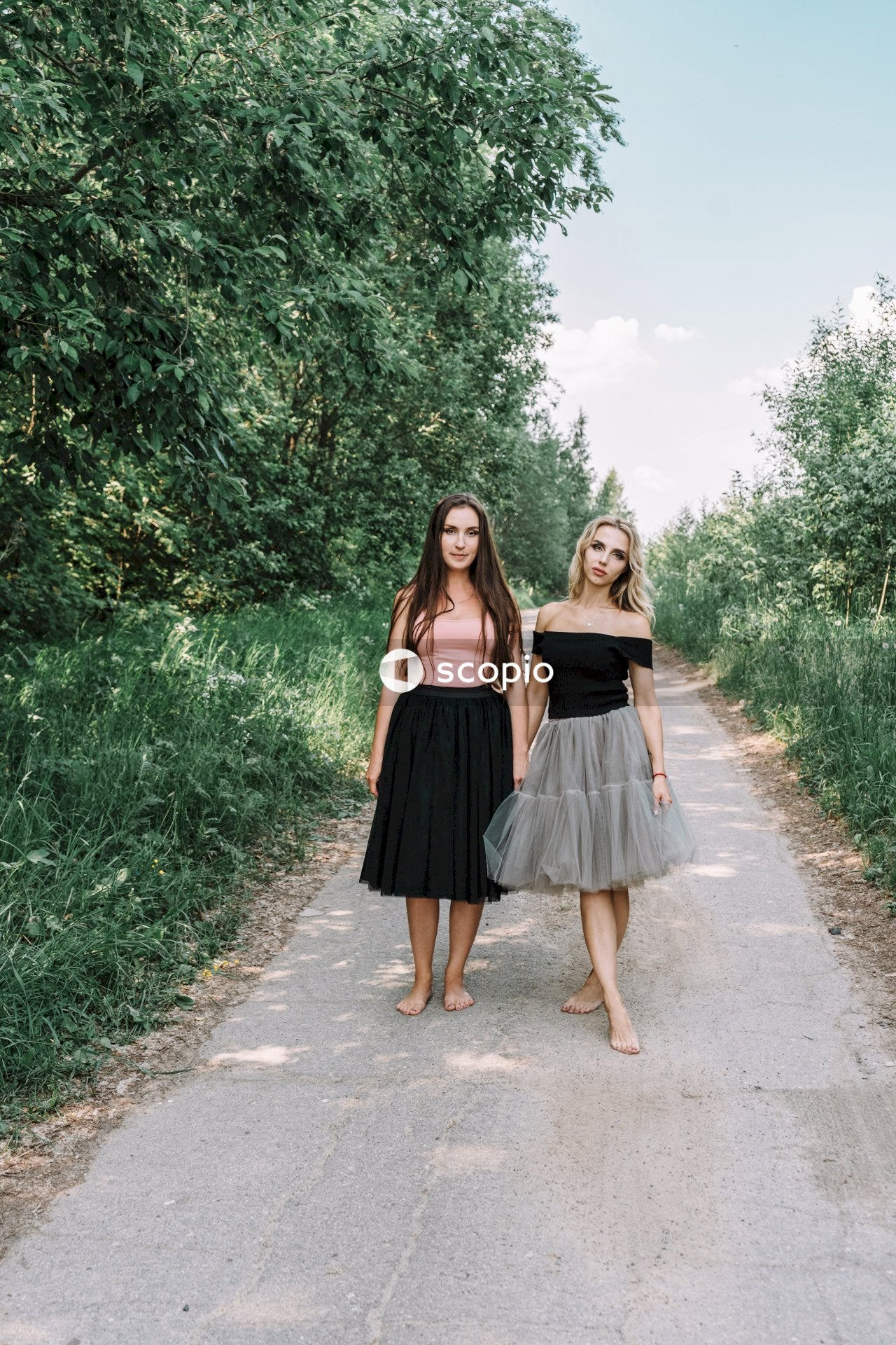 Two women standing near trees