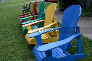 Blue and yellow wooden armchair on green grass field