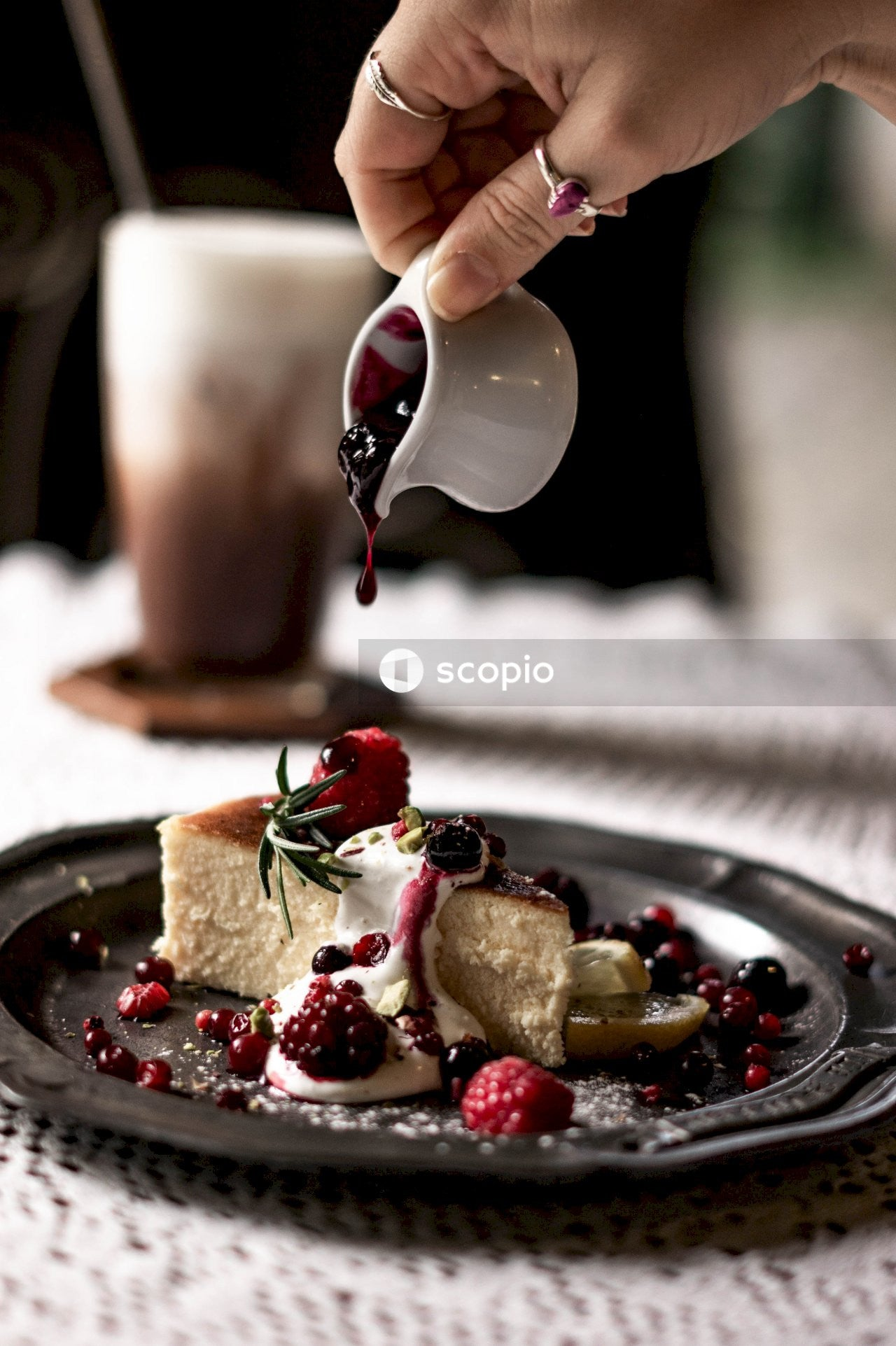Person pouring red liquid on chocolate cake