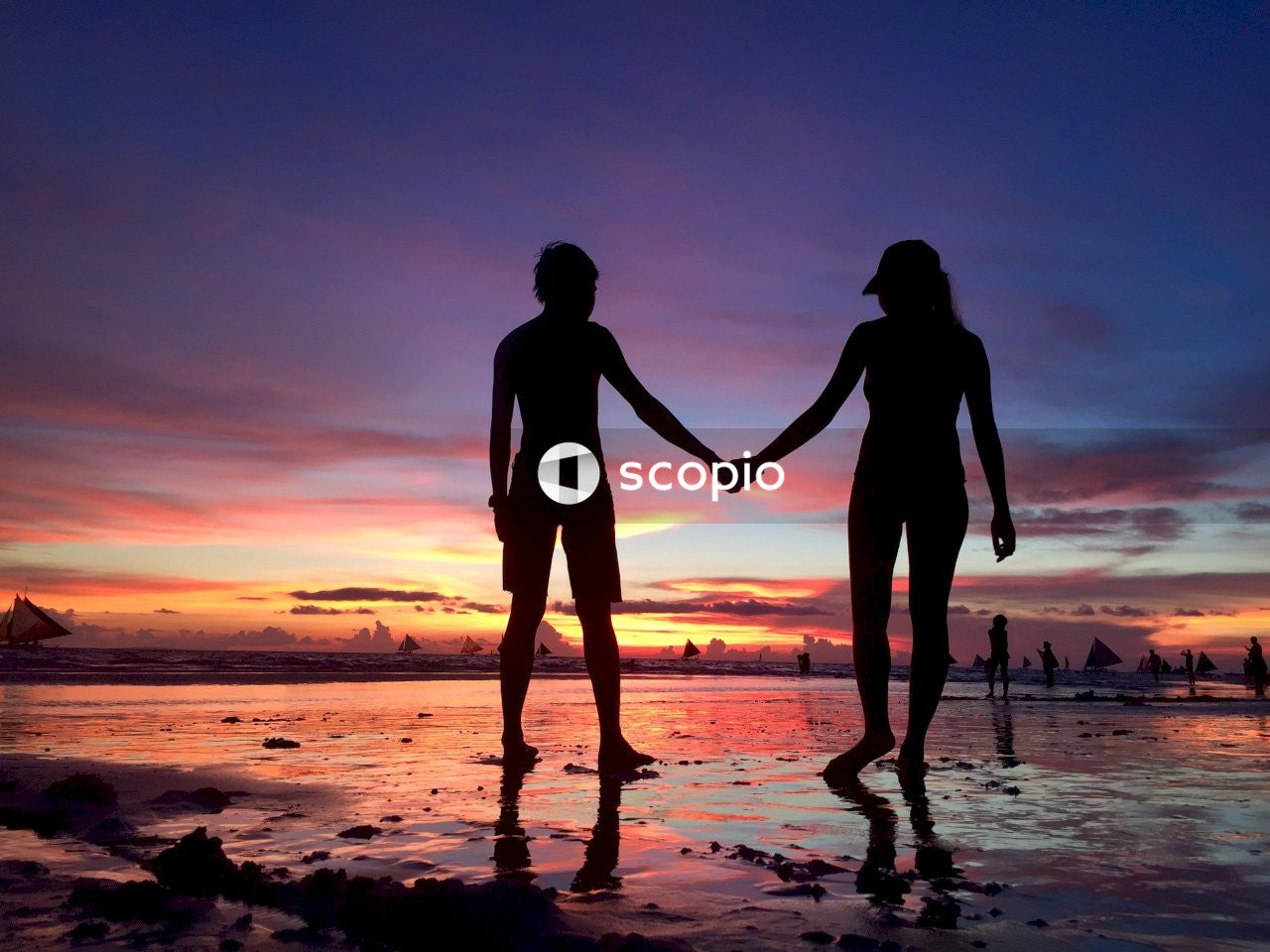 Silhouette of couple walking on beach during sunset