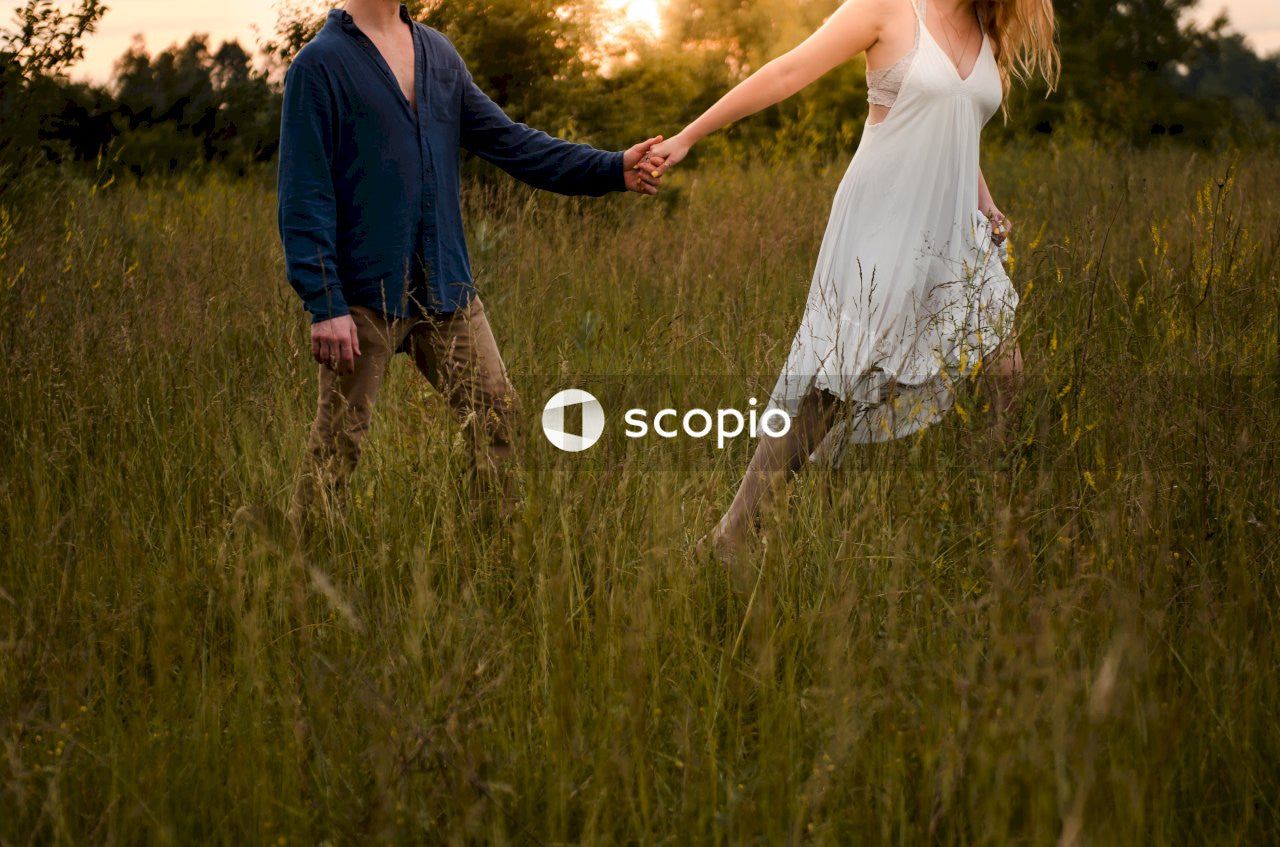 Woman holding man's hand walking on grass field