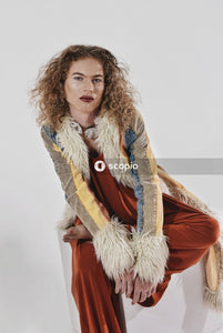 Woman in brown and white fur coat standing