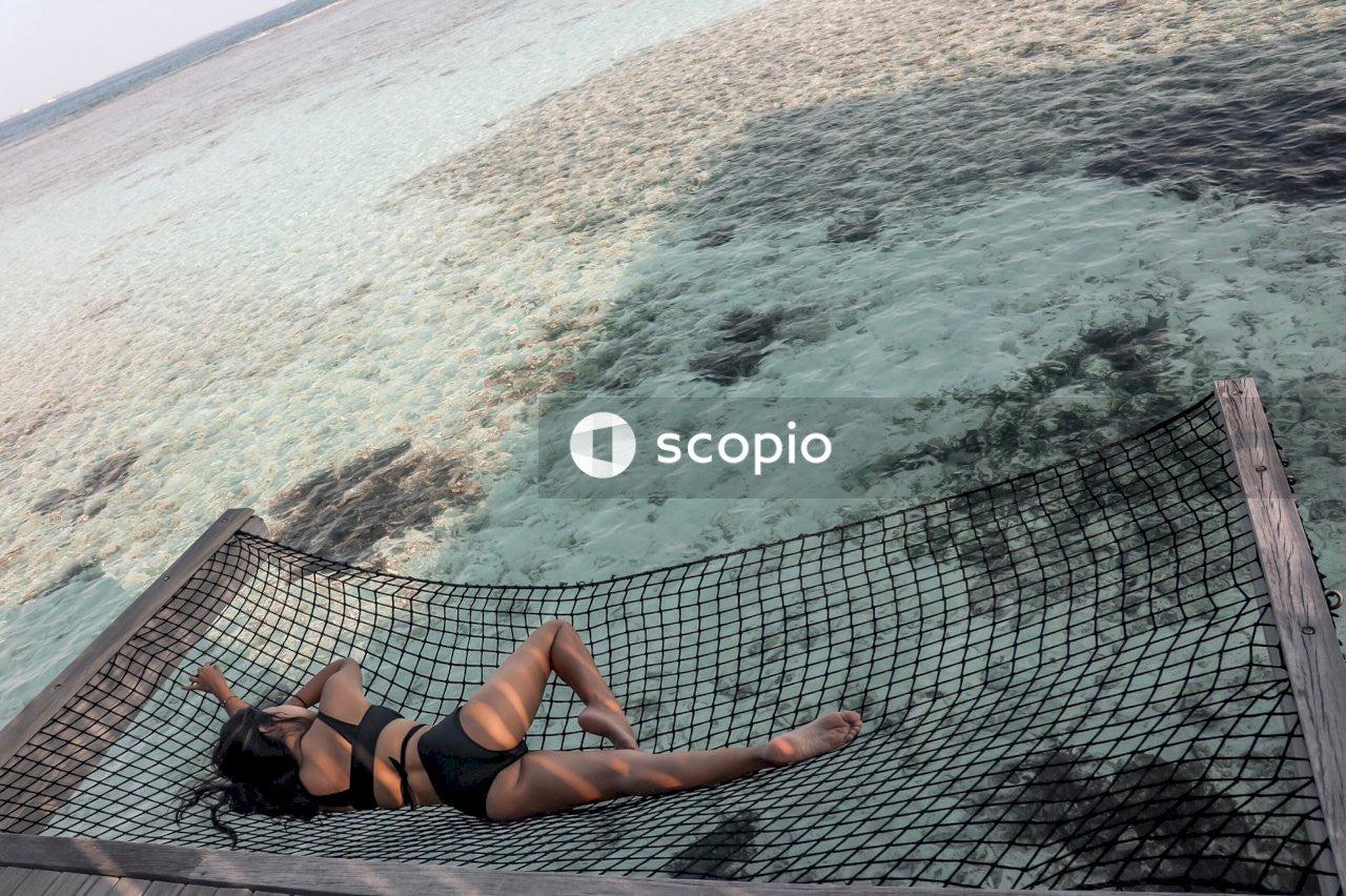 Woman on black bikini lying on black net hammock at the beach