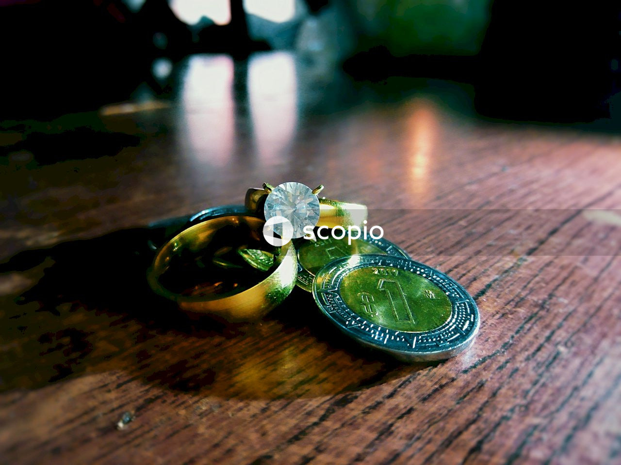 Coins and rings on wooden surface