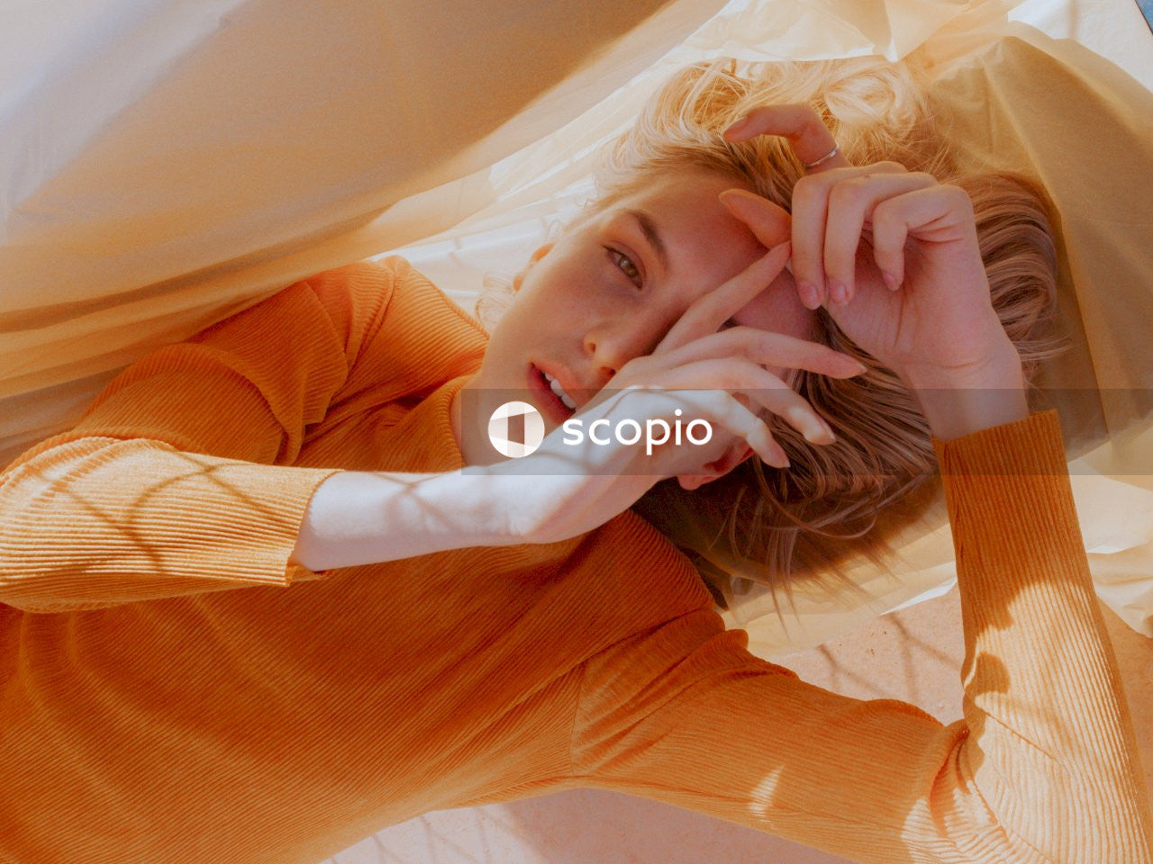 Woman in orange long sleeve shirt lying on white textile