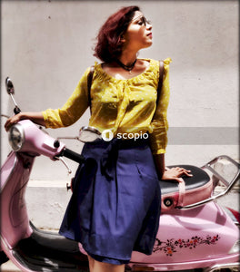 Woman in yellow long sleeve shirt and blue skirt riding on red motor scooter