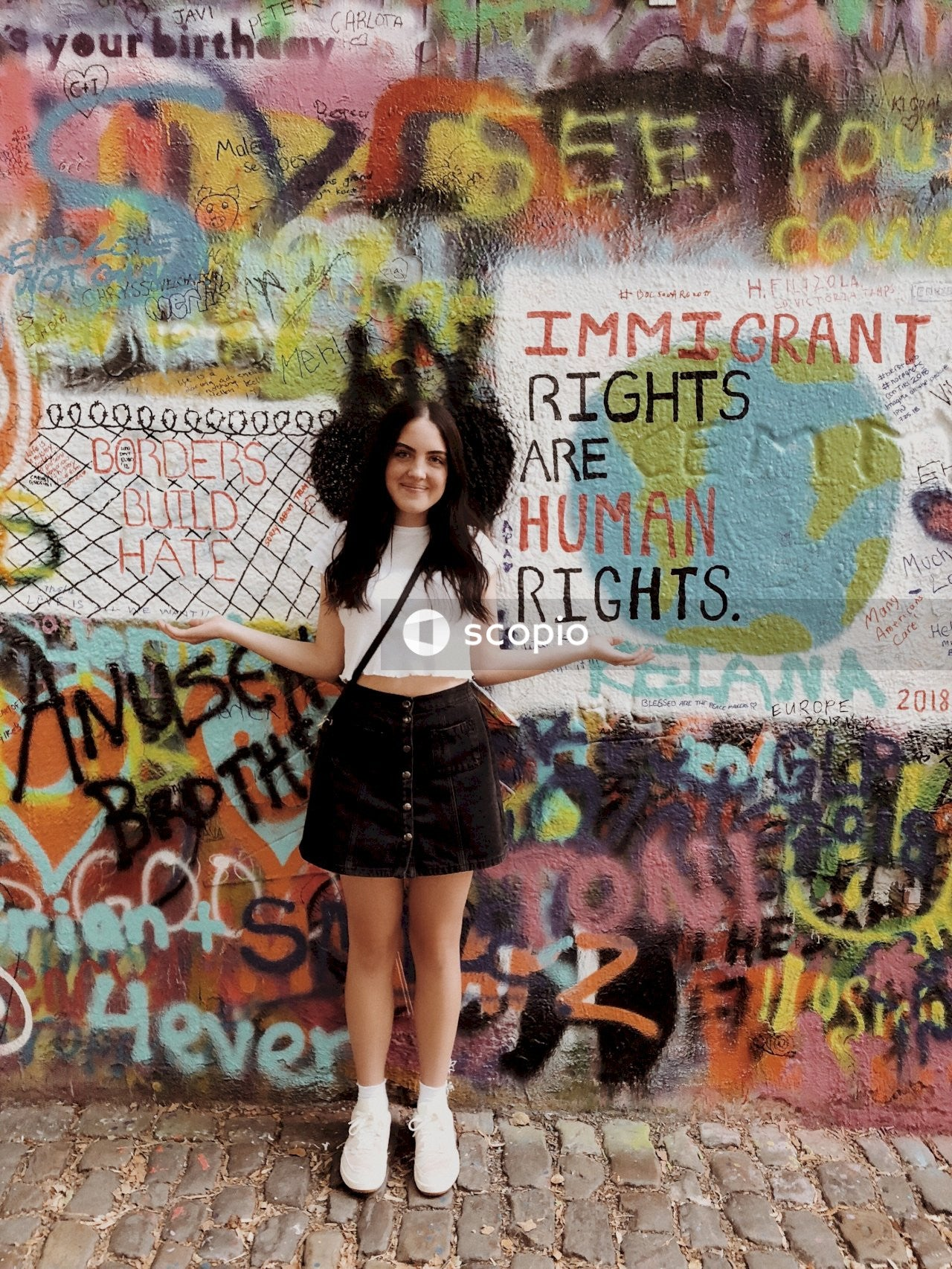 Woman in black mini skirt standing near graffiti wall