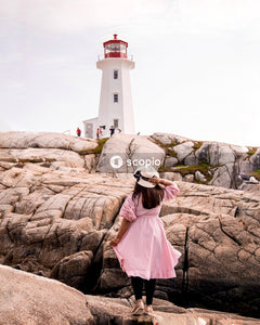 Woman in pink dress standing on brown rock near white and red lighthouse