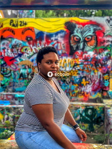 Woman in black and white stripe shirt standing near graffiti wall