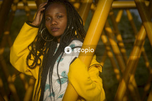 Woman in yellow coat standing beside yellow metal bar