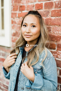 Woman in blue denim jacket leaning on brown brick wall