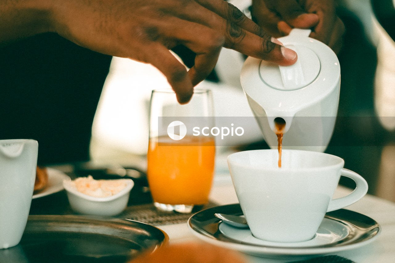 Person pouring white liquid on white ceramic teacup