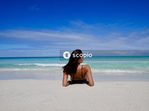 Woman in black bikini sitting on beach