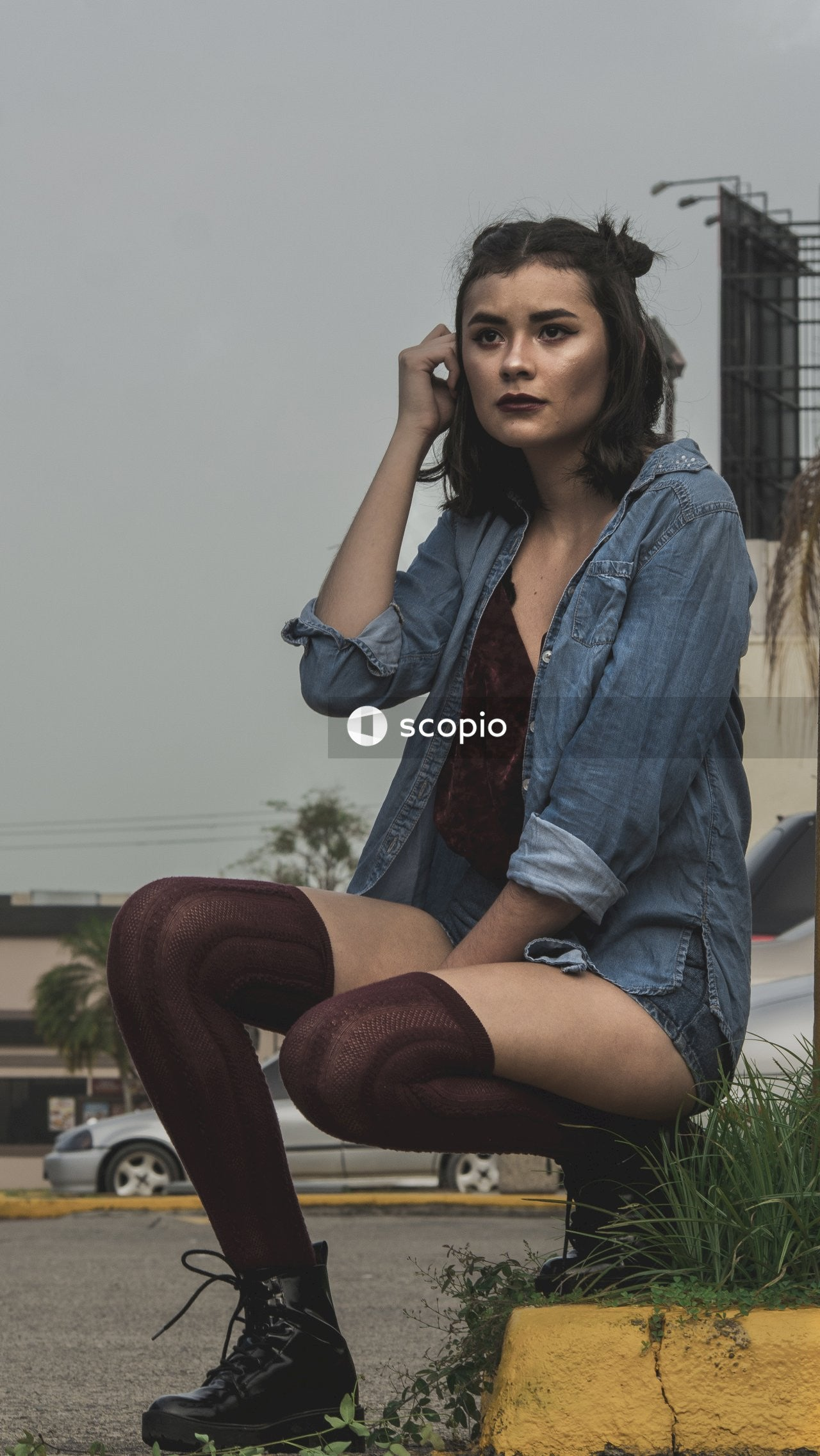 Woman in blue denim jacket and red mini skirt sitting on brown wooden bench