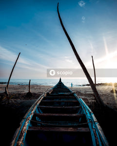 Blue and white boat on beach during sunset