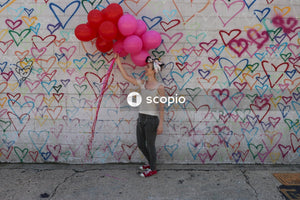 Woman holds balloon and stands near wall
