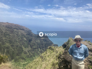 Man in blue jacket and white cap standing on cliff