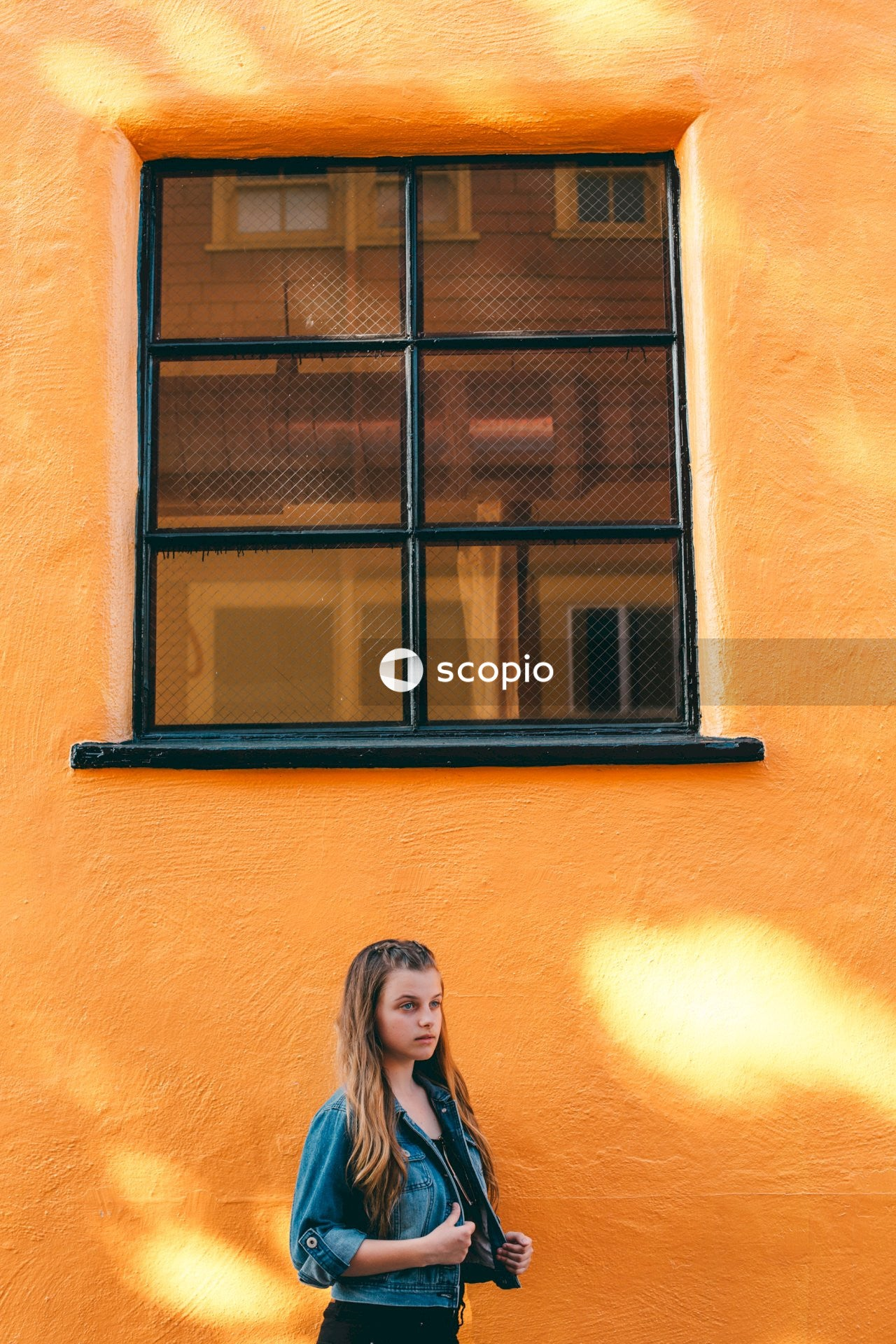 Woman in black shirt standing beside window