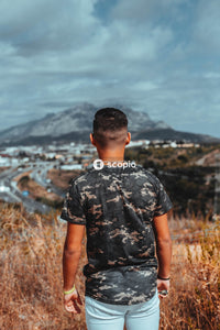 Man in black and gray camouflage crew neck t-shirt standing on brown grass field