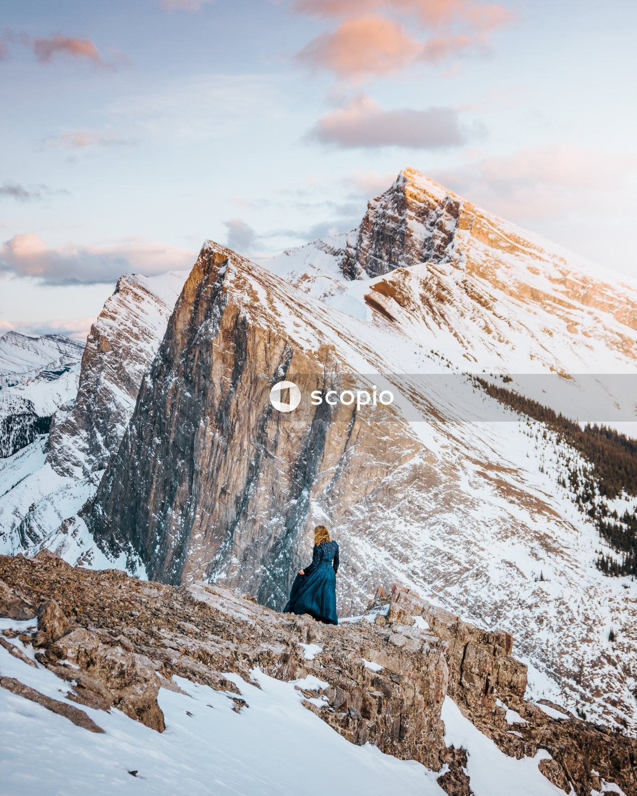 Person in blue jacket sitting on snow covered ground near snow covered mountain