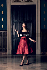 Woman in black and red dress standing near brown wooden door