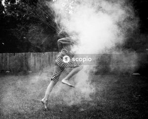 Grayscale photo of person about to jump on white smoke