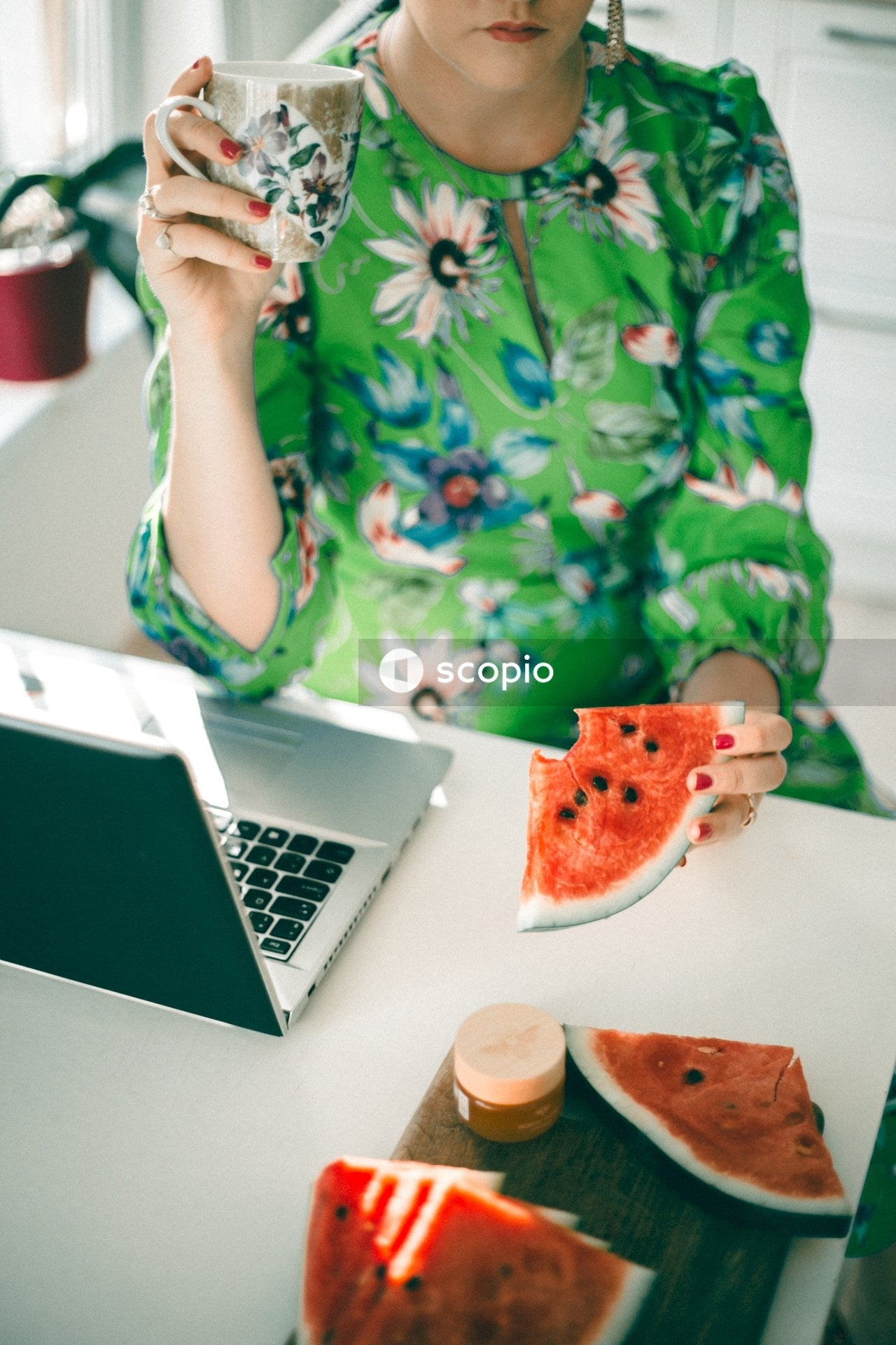 Woman in green and white floral dress holding sliced watermelon