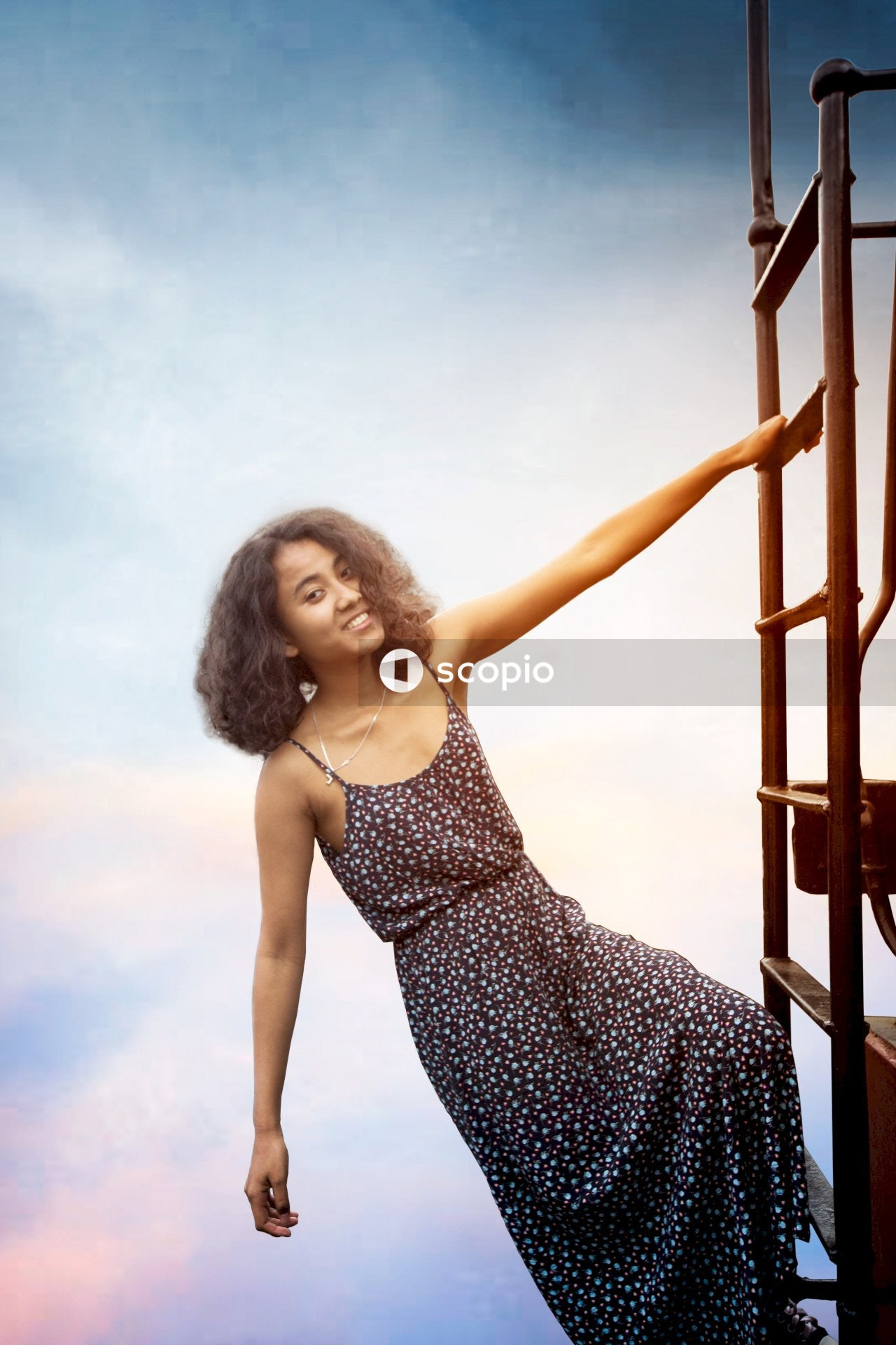 Woman in black and white polka dot spaghetti strap dress standing on ladder