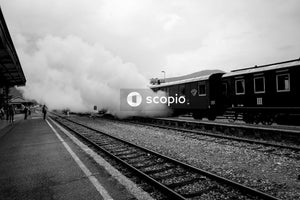 Grayscale photo of train on rail tracks