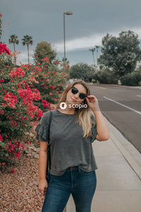 Woman in black crew neck t-shirt and blue denim shorts standing on road