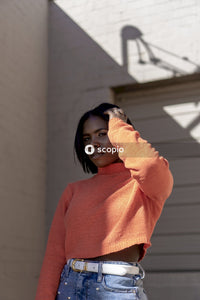 Woman in orange turtleneck sweater