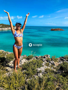 Woman in blue and white bikini standing on rock near body of water