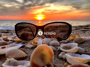 Black framed sunglasses on white and gray stones on beach during sunset